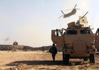 U.S. Army Special Operations Soldiers, assigned to the Combined Joint Special Operations Task Force – Afghanistan, arrive in a Family of Medium Tactical Vehicle at a staging area on an undisclosed forward operating base in Helmand Province as two CH-47 Chinook helicopters fly overhead.